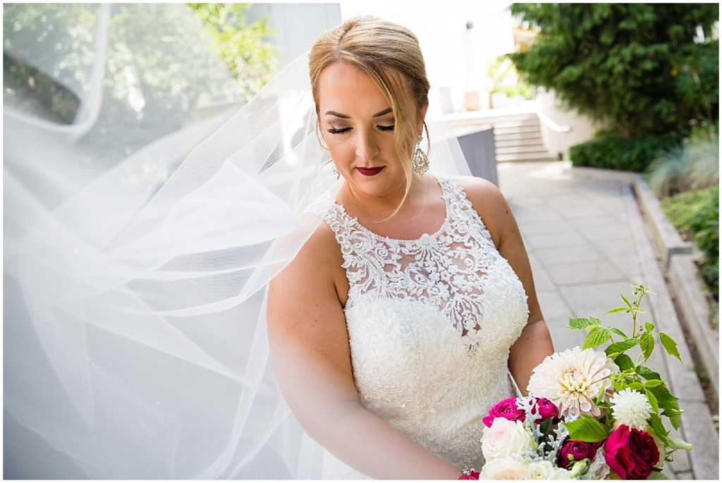 Bride in beaded gown holds an ivory, red, and blush flower bouquet while her long veil blows in the wind, Sodo Park wedding, Seattle wedding planner, Perfectly Posh Events, Photo by La Vie Photography