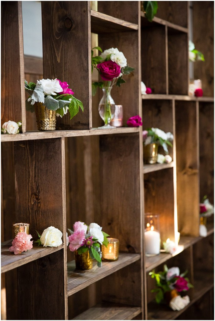 Wooden bookshelves covered with white candles and small vases with ivory, red, and pink flowers, Sodo Park wedding, Seattle wedding planner, Perfectly Posh Events, Photo by La Vie Photography