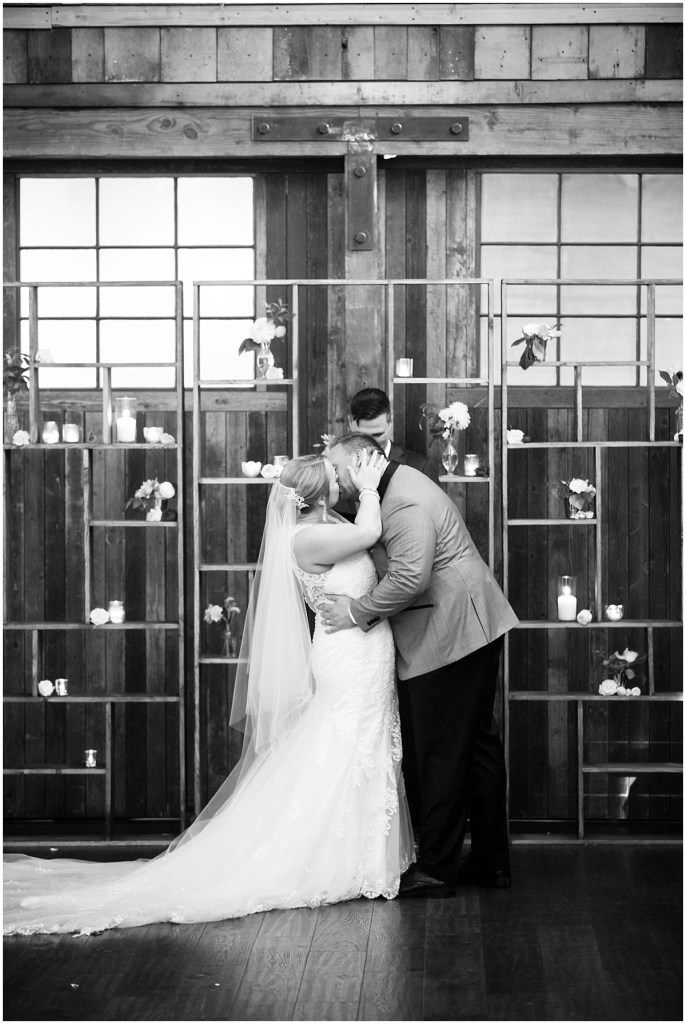 Black and white photo of bride and groom sealing their vows with a kiss in front of a rustic wood backdrop with bookshelves covered candles and vases, Sodo Park wedding, Seattle wedding planner, Perfectly Posh Events, Photo by La Vie Photography