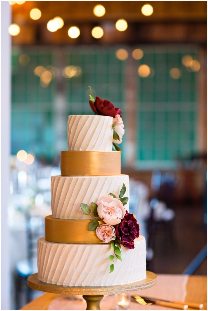 Five tier wedding cake with alternating gold and ivory colored frosting layers accessorized with red and blush flowers, Sodo Park wedding, Seattle wedding planner, Perfectly Posh Events, Photo by La Vie Photograph