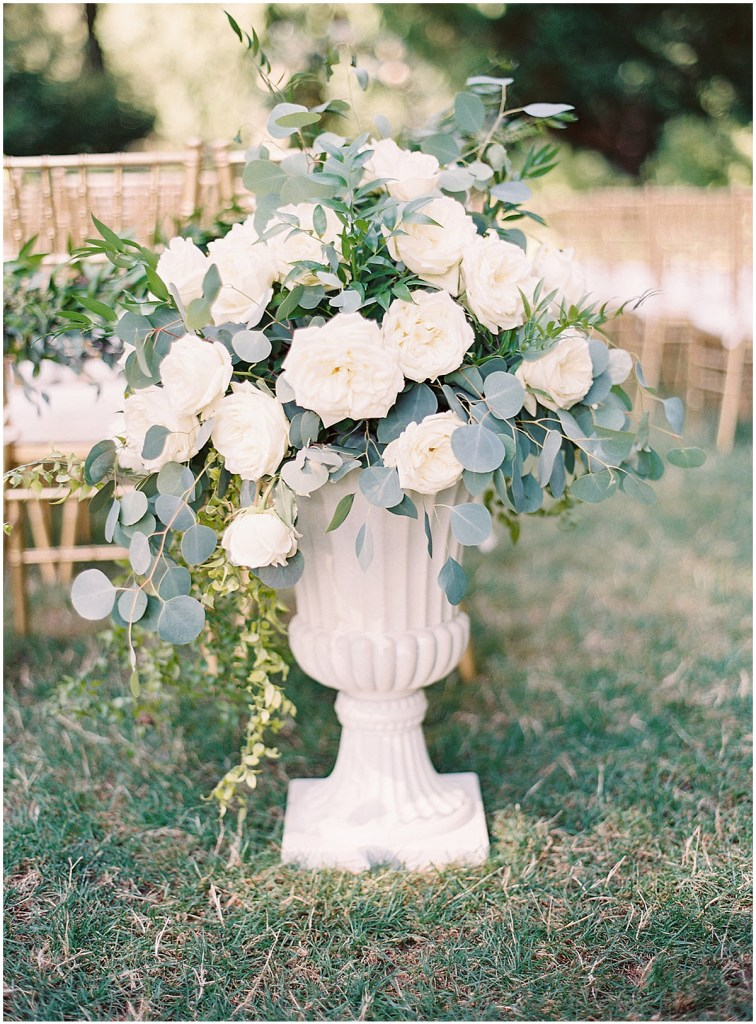 A large urn filled with ivory and blush florals and greenery anchors the front end of a wedding aisle, DeLille Cellars wedding, Woodinville wedding, Perfectly Posh Events wedding coordination, Photo by Great Romance Photography