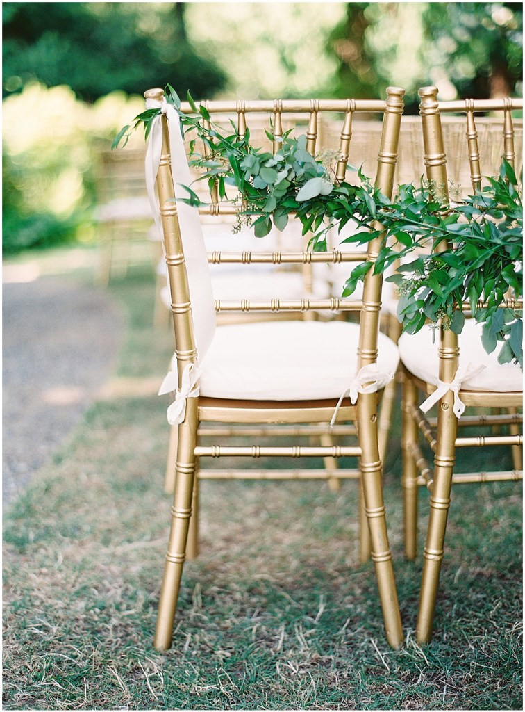 Close up of gold wedding ceremony chairs decorated with green vines, DeLille Cellars wedding, Woodinville wedding, Perfectly Posh Events wedding coordination, Photo by Great Romance Photography