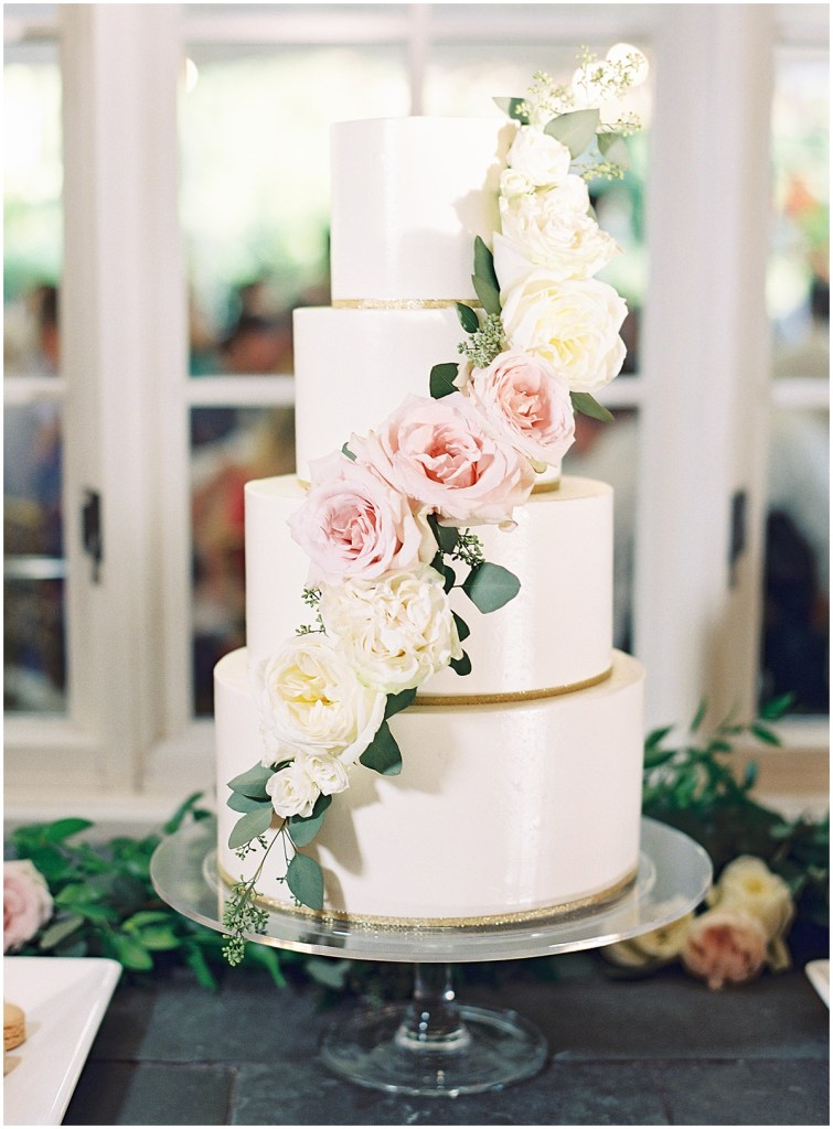 Four tier wedding cake decorated in white frosting and gold accents and covered in ivory and blush flowers with touches of greenery, DeLille Cellars wedding, Woodinville wedding, Perfectly Posh Events wedding coordination, Photo by Great Romance Photography