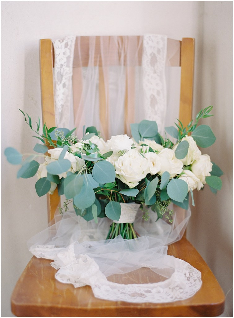 Large bridal bouquet with ivory flowers and greenery sits on a chair with a long sheer veil, DeLille Cellars wedding, Woodinville wedding, Perfectly Posh Events wedding coordination, Photo by Great Romance Photography