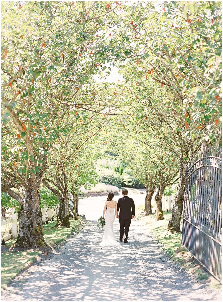Bride and groom walk down a pathway lined with blooming trees, DeLille Cellars wedding, Woodinville wedding, Perfectly Posh Events wedding coordination, Photo by Great Romance Photography