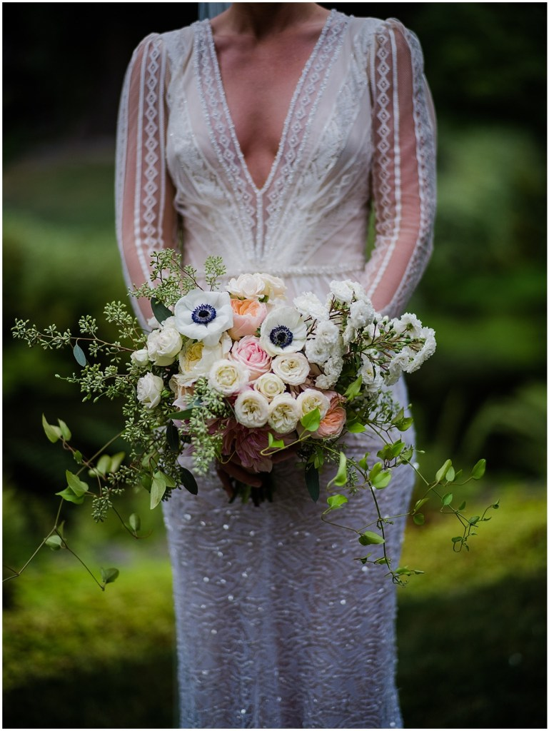 Close up of bride in an ivory gown featuring lace and beading holding a large bouquet of ivory and blush colored flowers, DeLille Cellars wedding, Washington wedding planner, Perfectly Posh Events, Photo by Shane Macomber Photography