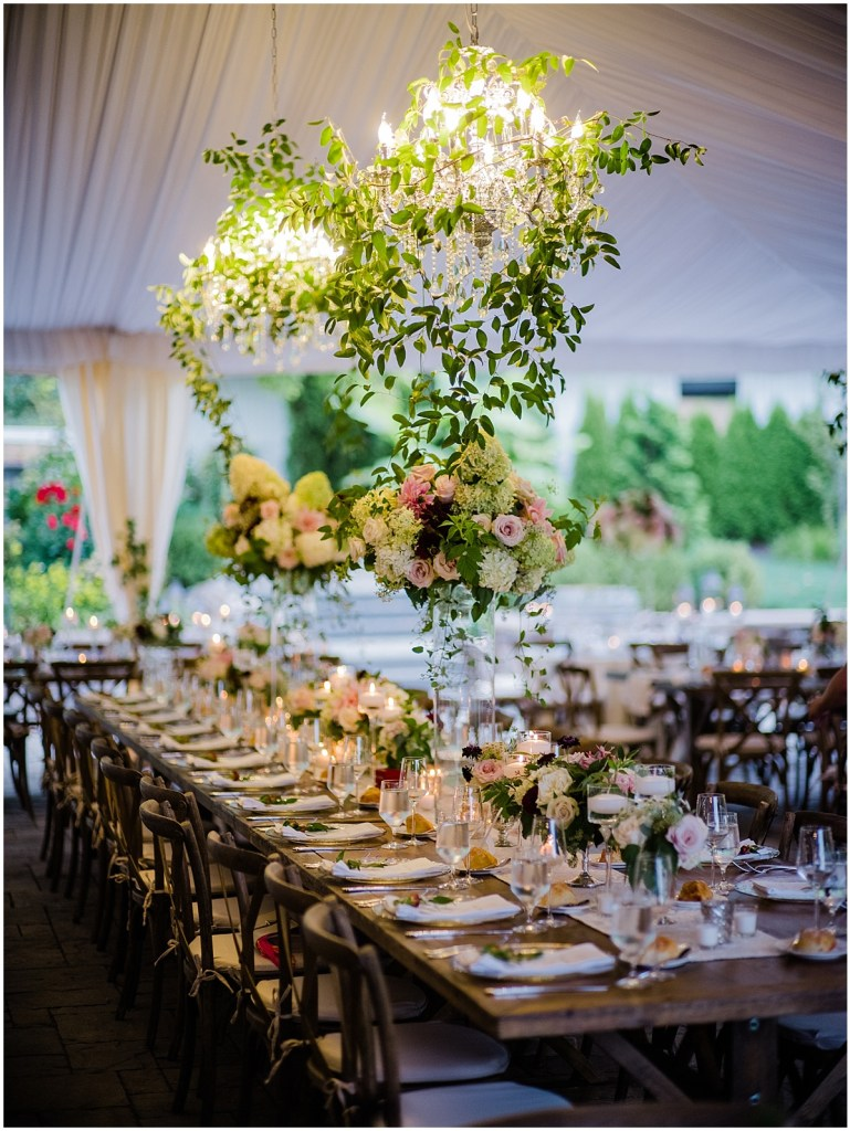 Long, rustic wood wedding reception dinner table featuring tall glass floral vases with two chandeliers covered in vines hanging overhead, DeLille Cellars wedding, Washington wedding planner, Perfectly Posh Events, Photo by Shane Macomber Photography