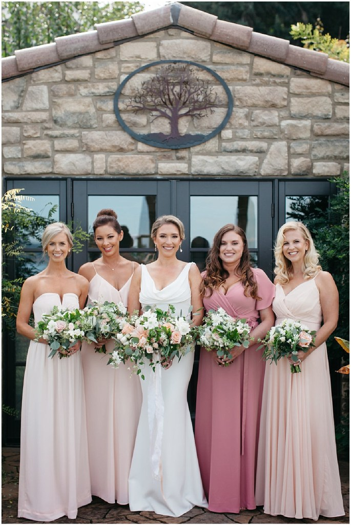 Bride poses with her bridesmaids wearing gowns in differing shades of blush and pink while holding ivory and blush pink floral bouquets, PNW outdoor summer wedding, Washington wedding designer, Perfectly Posh Events, Photo by Kate Price Photography