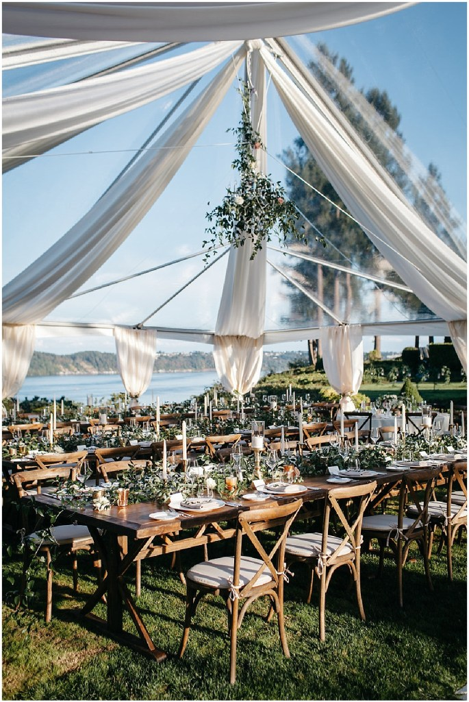 Wedding reception rustic wood tables and dinner chairs decorated with greenery and pink flowers and white candles set up under a large white tent with greenery hanging from the ceiling, PNW outdoor summer wedding, Washington wedding designer, Perfectly Posh Events, Photo by Kate Price Photography