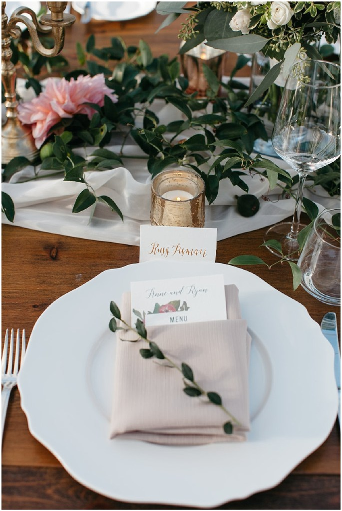 Wedding reception dinner setting on a rustic wood table with a folded tan napkin on a white plate, decorated with candles in gold candle holders and greenery, PNW outdoor summer wedding, Washington wedding designer, Perfectly Posh Events, Photo by Kate Price Photography