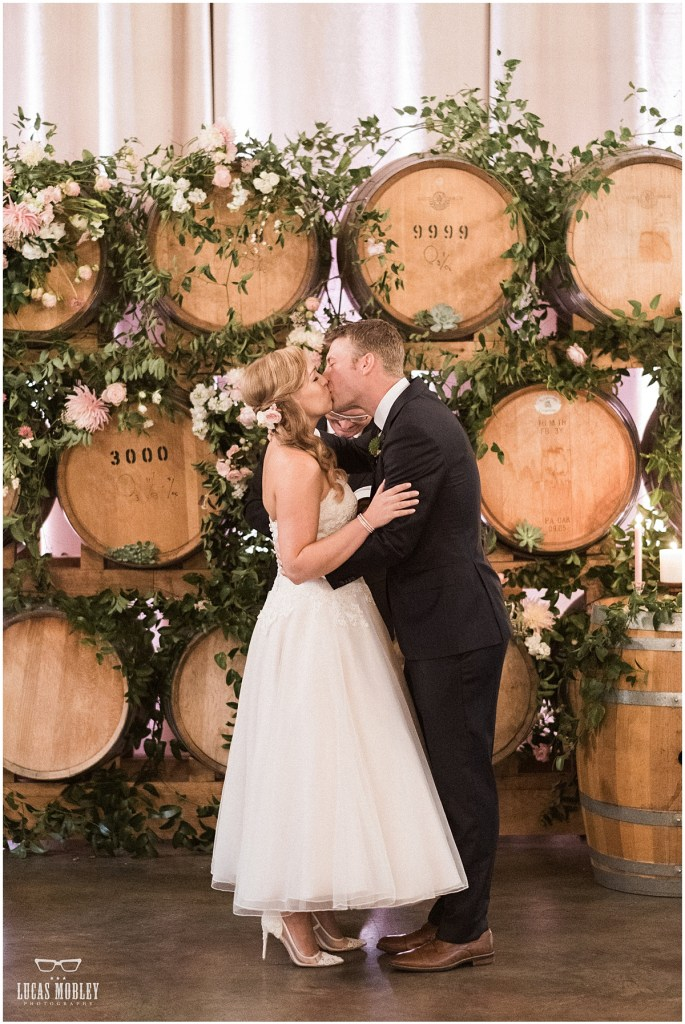 Bride and groom share a kiss after exchanging vows in front of an altar made of wood wine barrels decorated with greenery and touches of ivory and pink florals, The Foundry by Herban Feast wedding, fall wedding, Seattle wedding planner, Perfectly Posh Events, Photo by Lucas Mobley Photography