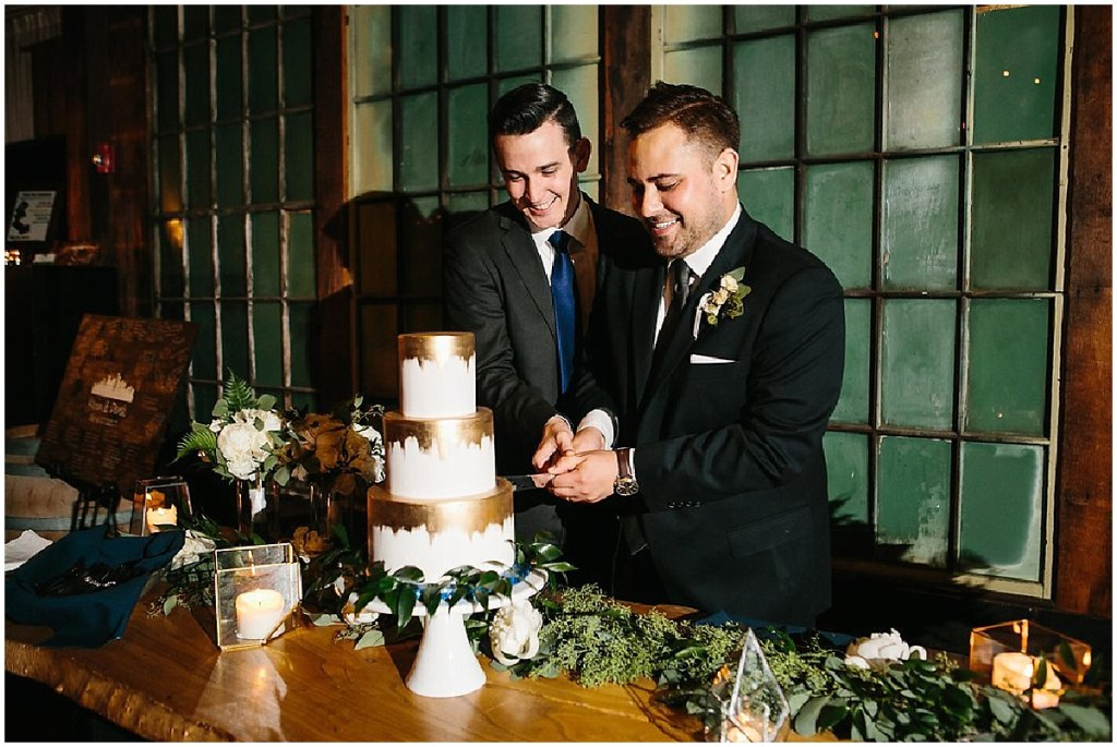 Two grooms cut into their three tier wedding cake decorated in white and gold frosting, same sex wedding, Sodo Park wedding, Seattle wedding coordinator, Perfectly Posh Events, Photo by Melissa Kilner Photography