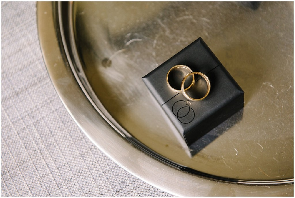Two gold wedding bands sit on black box on a silver tray, same sex wedding, Sodo Park wedding, Seattle wedding coordinator, Perfectly Posh Events, Photo by Melissa Kilner Photography