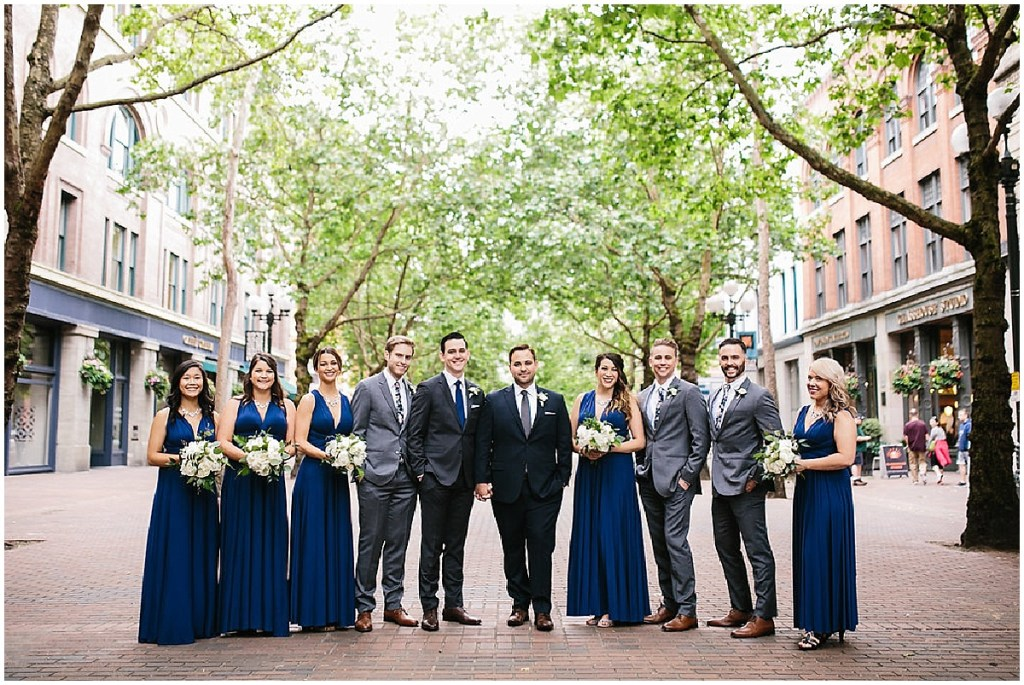 Grooms in navy suits pose outside in Pioneer Square with their groomsmen and bridesmaids, same sex wedding, Sodo Park wedding, Seattle wedding coordinator, Perfectly Posh Events, Photo by Melissa Kilner Photography
