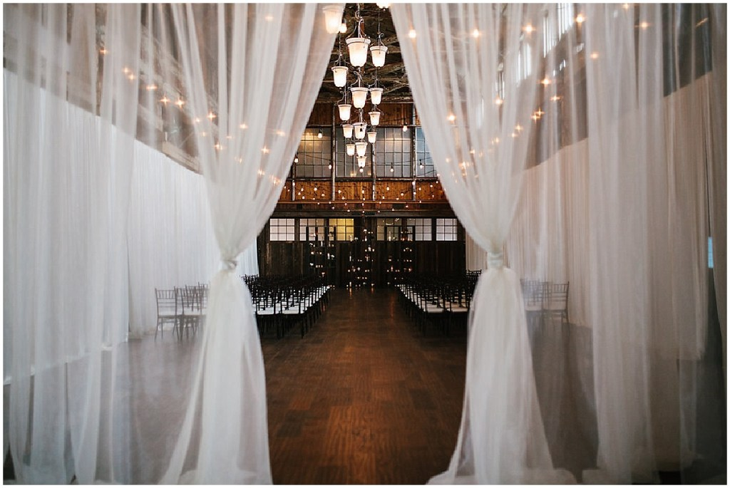 A peak through a sheer, white curtain at an indoor wedding ceremony set up with dark wood chairs and cafe lights hanging from the ceiling, same sex wedding, Sodo Park wedding, Seattle wedding coordinator, Perfectly Posh Events, Photo by Melissa Kilner Photography