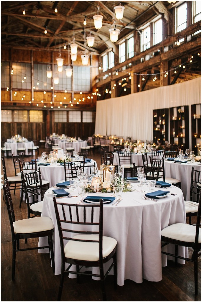 Round wedding reception dinner tables covered in white table cloths and navy napkins and surrounded with dark wood chairs, same sex wedding, Sodo Park wedding, Seattle wedding coordinator, Perfectly Posh Events, Photo by Melissa Kilner Photography