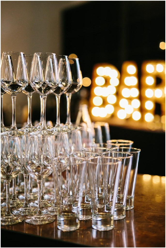 Pint glasses and wine glasses are stacked on a bar with a light up bar sign in the background, same sex wedding, Sodo Park wedding, Seattle wedding coordinator, Perfectly Posh Events, Photo by Melissa Kilner Photography