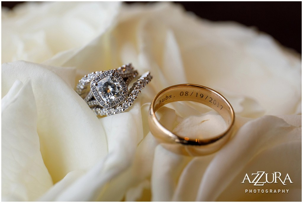 Close up of bride's cushion cut engagement ring with halo diamond band and two eternity wedding bands along with the groom's gold wedding band with the couple's wedding date engraved inside, Four Seasons wedding, Seattle wedding, Perfectly Posh Events event coordination, Photo by Azzura Photography