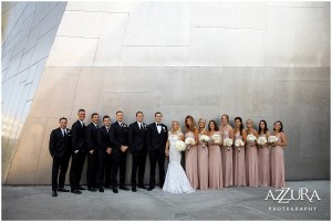 Bride and groom pose outside with their bridesmaids in blush colored gowns and groomsmen in black tuxedos in front of a large metal wall outside Seattle's Museum of Pop (fka the Experience Music Project), Four Seasons wedding, Seattle wedding, Perfectly Posh Events event coordination, Photo by Azzura Photography