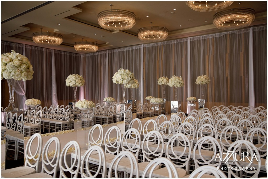 An all-white wedding ceremony setup indoors with white chairs and a raised runway framed with large ivory floral bouquets sitting on lucite pillars, Four Seasons wedding, Seattle wedding, Perfectly Posh Events event coordination, Photo by Azzura Photography