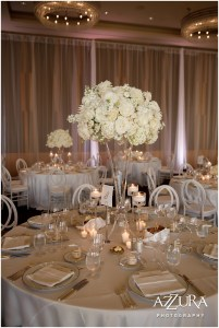 A floral bouquet bursting with ivory colored flowers in an extra tall vase serves as a centerpiece on a table decorated with white table cloth and candles, Four Seasons wedding, Seattle wedding, Perfectly Posh Events event coordination, Photo by Azzura Photography