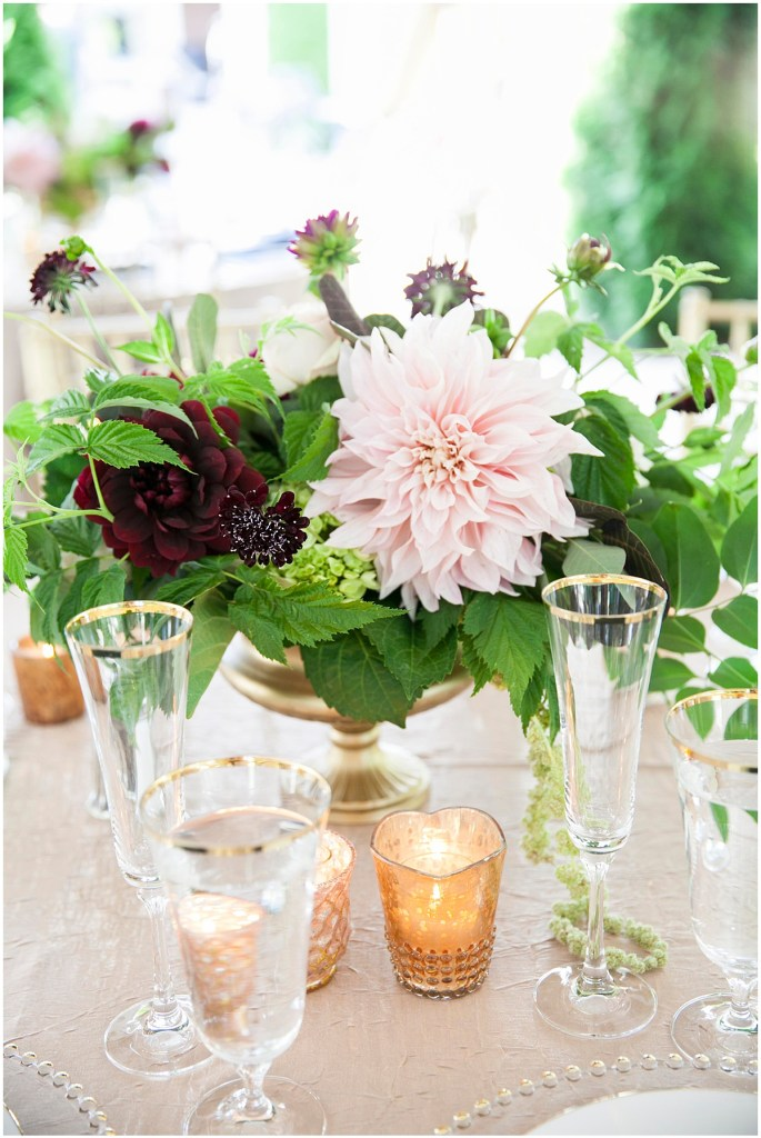 Wedding reception table centerpiece made of blush pink and burgundy flowers with touches of greenery in a gold vase accented with votive candles in gold mercury glass candle holders, Laurel Creek Manor wedding, Perfectly Posh Events wedding coordination, Photo by Katie Parra Photography