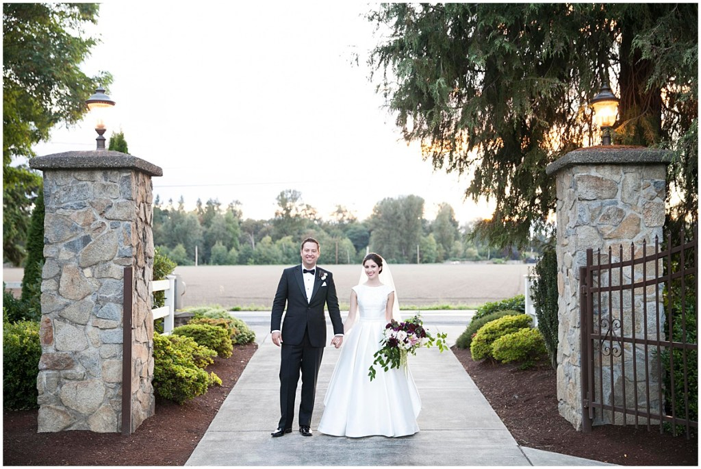 Bride holding a large ivory and burgundy bouquet holds hands with her groom while they stand between iron and stone gates, Laurel Creek Manor wedding, Perfectly Posh Events wedding coordination, Photo by Katie Parra Photography