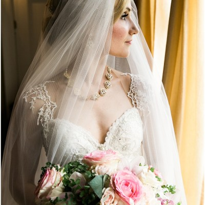 Bride poses indoors wearing a custom beaded ballgown and a sheer veil while holding a large bouquet made of ivory and blush pink flowers with touches of greenery, Pacific Northwest wedding, Thornewood Castle wedding, wedding planning by Perfectly Posh Events, Photo by Stephanie Cristalli