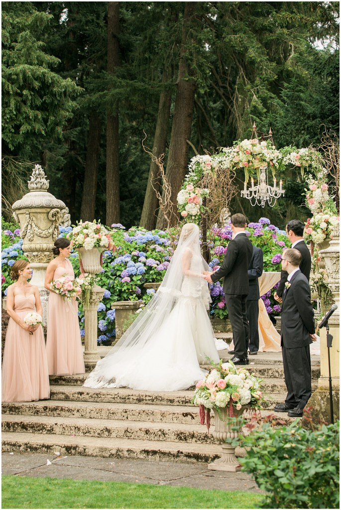 Bride and groom exchange vows in front of guests during their outdoor garden ceremony, Pacific Northwest wedding, Thornewood Castle wedding, wedding planning by Perfectly Posh Events, Photo by Stephanie Cristalli