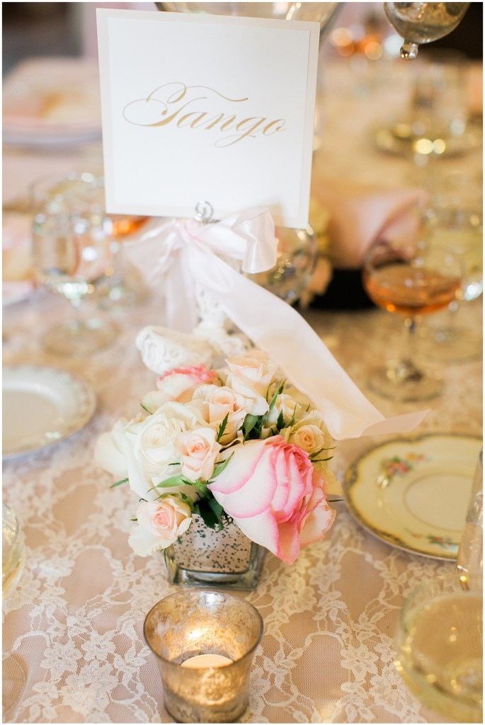 Wedding reception table centerpiece with custom made table number in gold lettering, ivory and pink floral arrangements, and covered with an ivory lace table cloth, Pacific Northwest wedding, Thornewood Castle wedding, wedding planning by Perfectly Posh Events, Photo by Stephanie Cristalli