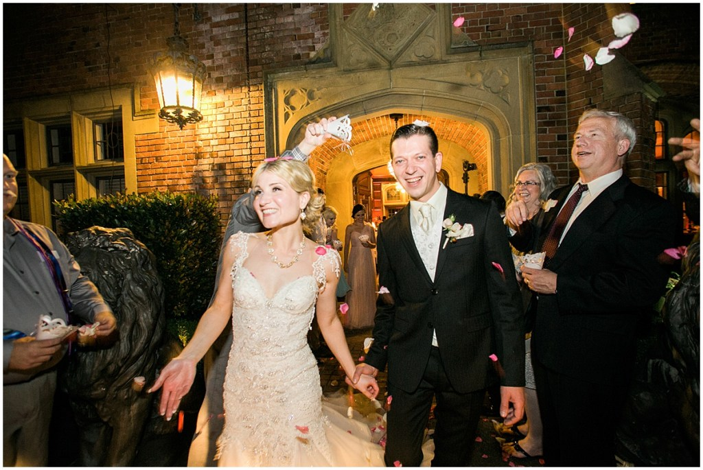 Bride and groom smile as they depart their wedding while their guests shower them with rose petals, Pacific Northwest wedding, Thornewood Castle wedding, wedding planning by Perfectly Posh Events, Photo by Stephanie Cristalli