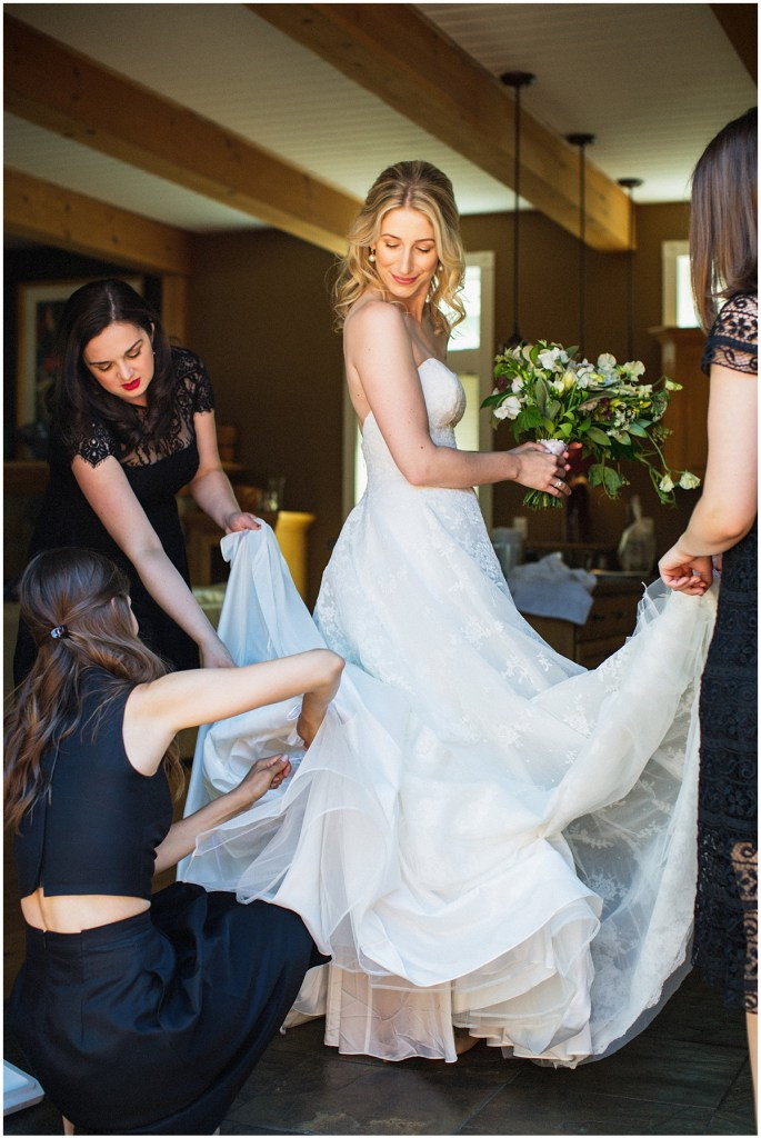 Bride prepares for her wedding day while her bridesmaids help adjust the train of her off-white, strapless wedding gown, urban wedding, Within Sodo wedding, Seattle event planner, Perfectly Posh Events, Photo by Jenny J Photography