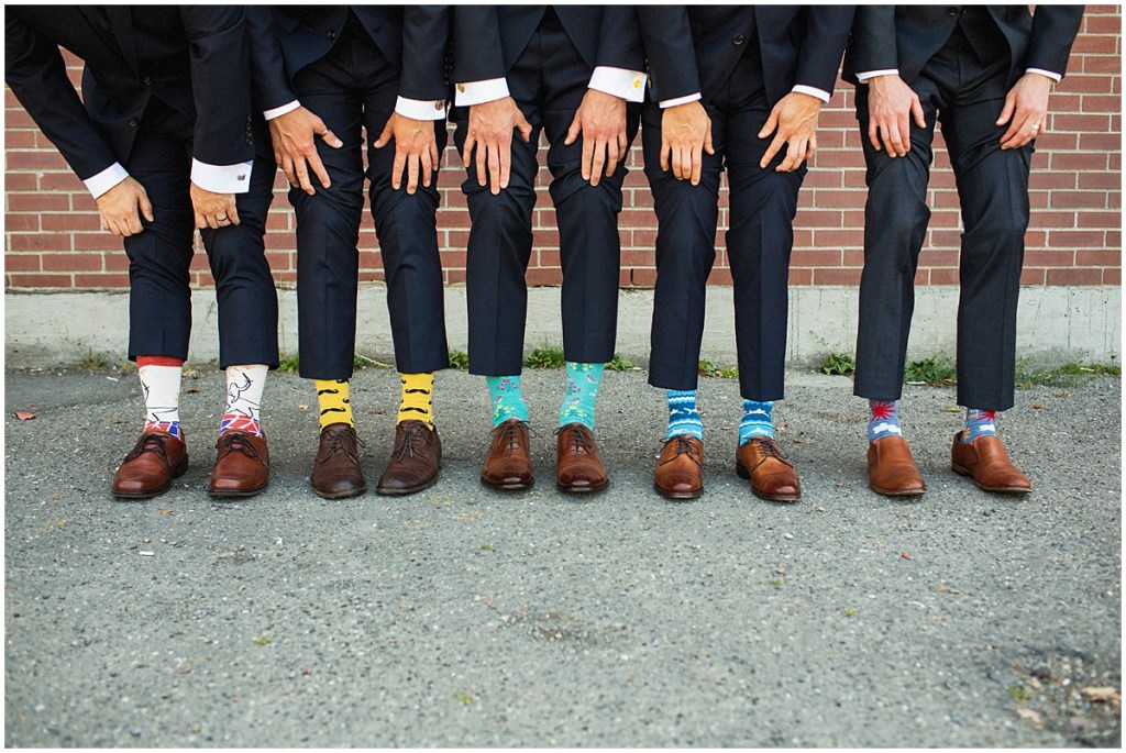 Groom and groomsmen in navy suits and brown shoes show off their colorful and uniquely patterned socks, urban wedding, Within Sodo wedding, Seattle event planner, Perfectly Posh Events, Photo by Jenny J Photography