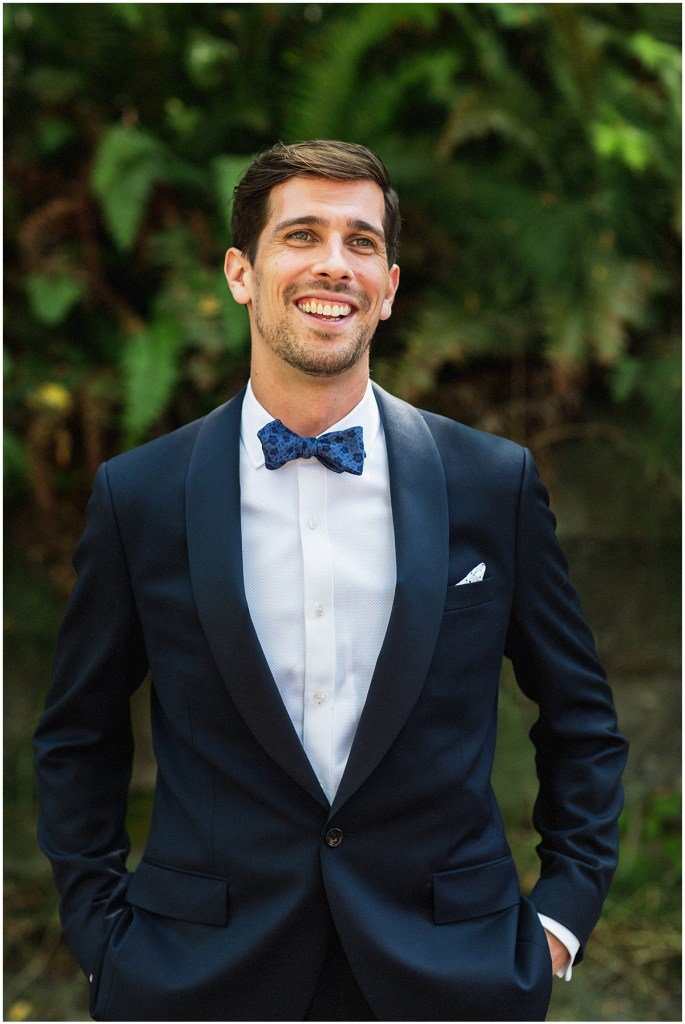 Groom posed outside while wearing a navy suit with a blue patterned bow tie, urban wedding, Within Sodo wedding, Seattle event planner, Perfectly Posh Events, Photo by Jenny J Photography