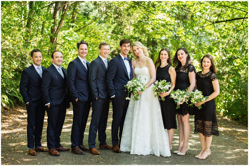 Bride and groom pose with the bridesmaids in black lace dresses and groomsmen in navy suits outside under trees, urban wedding, Within Sodo wedding, Seattle event planner, Perfectly Posh Events, Photo by Jenny J Photography