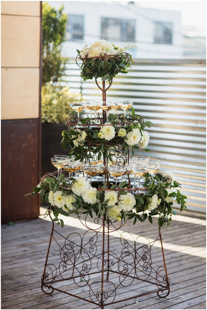A three-tier brass champagne towers filled with glasses of champagne and decorated with plenty of ivory flowers and greenery, urban wedding, Within Sodo wedding, Seattle event planner, Perfectly Posh Events, Photo by Jenny J Photography