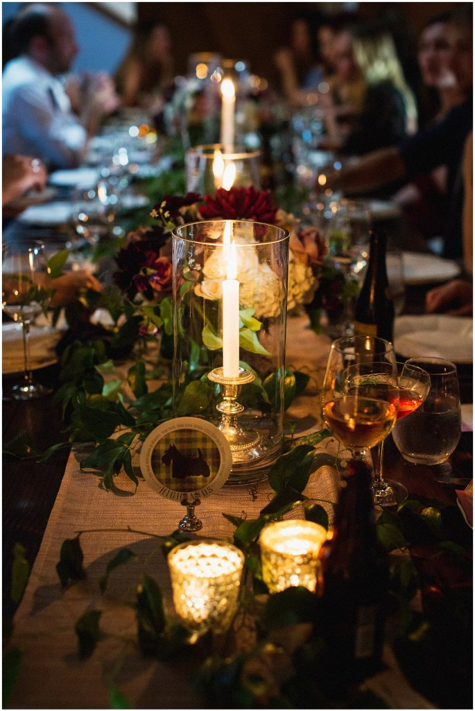 A dark and moody wedding reception table is set up with burgundy flowers and greenery along with candles in mercury votives and large hurricane holders, urban wedding, Within Sodo wedding, Seattle event planner, Perfectly Posh Events, Photo by Jenny J Photography