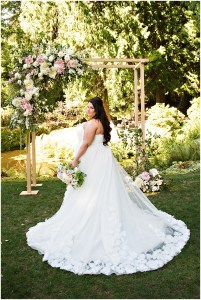 A back view of a bride in her off-white, long, ball gown style wedding dress with a wooden wedding ceremony altar covered in flowers in the background, DeLille Cellars wedding, Woodinville winery, Washington wedding, Perfectly Posh Events wedding planning, Photo by Barbie Hull
