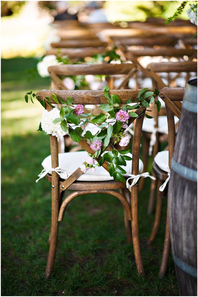 A back view of rustic wood chairs set up for an outdoor wedding ceremony decorated with greenery and pops of ivory and pink flowers, DeLille Cellars wedding, Woodinville winery, Washington wedding, Perfectly Posh Events wedding planning, Photo by Barbie Hull