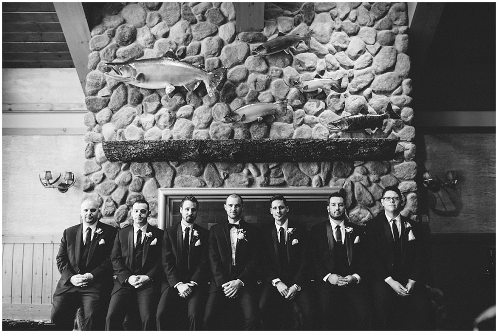 Black and white photo of groom posing with his groomsmen in black tuxedos sitting beneath a rustic stone fireplace decorated with fish figurines, Edgewater Hotel, Seattle wedding, Washington wedding coordinator, Perfectly Posh Events, Photo by Carina Skrobecki