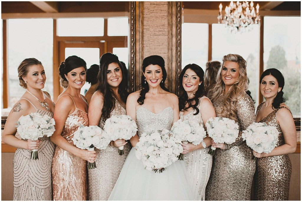 A bride poses with bridesmaids wearing sequined gowns in varying shades of gold and champagne while holding white floral bouquets, Edgewater Hotel, Seattle wedding, Washington wedding coordinator, Perfectly Posh Events, Photo by Carina Skrobecki