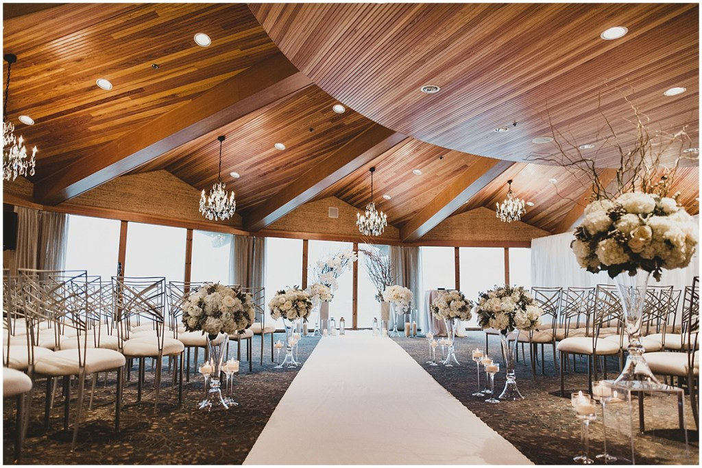 An indoor wedding ceremony set up with modern silver chairs, and a white carpet aisle lined with white bouquets in large glass vases leading to a rustic altar made of vines and branches and decorated with white flowers, Edgewater Hotel, Seattle wedding, Washington wedding coordinator, Perfectly Posh Events, Photo by Carina Skrobecki