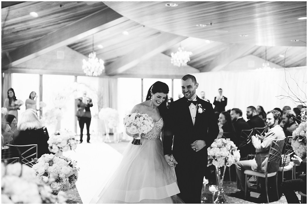 Black and white photo of bride and groom walking back down the aisle after exchanging vows as their guests cheer them on, Edgewater Hotel, Seattle wedding, Washington wedding coordinator, Perfectly Posh Events, Photo by Carina Skrobecki