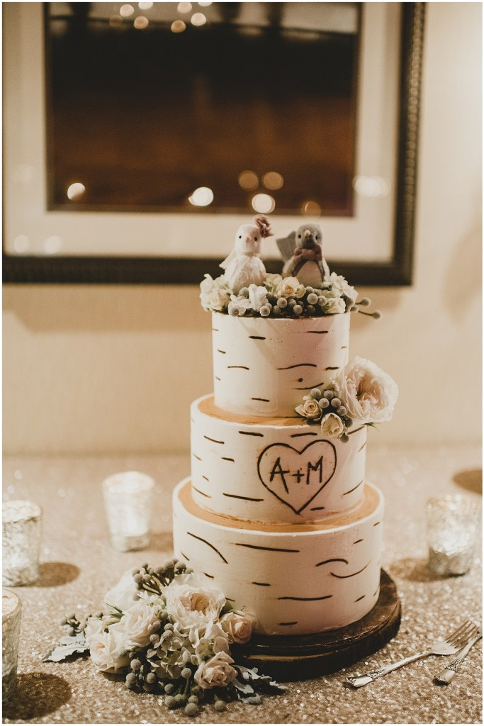 Three tier wedding cake covered in white frosting designed to look like a birch tree, top with bird