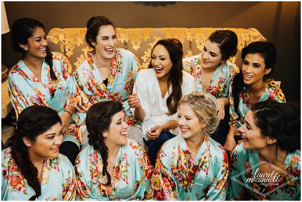 Bride in white satin robe laughs with her bridesmaids wearing blue floral satin robes while preparing for her wedding day, Fremont Foundry, Seattle wedding, Perfectly Posh Events wedding planning, Photo by Laurel McConnell Photography