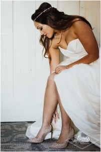 Bride in an off-white strapless wedding gown sits to put on her gold Christian Louboutin heels, Fremont Foundry, Seattle wedding, Perfectly Posh Events wedding planning, Photo by Laurel McConnell Photography