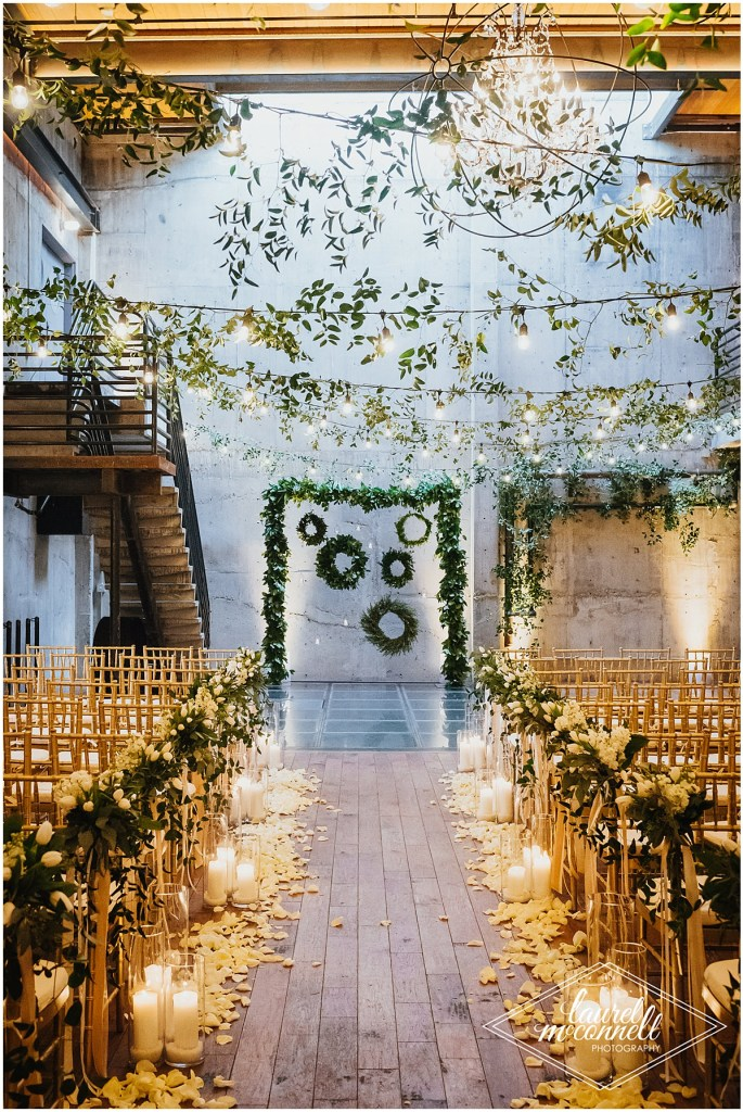 An urban indoor wedding ceremony set up with an altar covered in greenery with green wreaths hanging from it, rows of gold chairs draped with white flowers and greenery, and white pillar candles in hurricane holders and white rose petals lining the aisle, Fremont Foundry, Seattle wedding, Perfectly Posh Events wedding planning, Photo by Laurel McConnell Photography