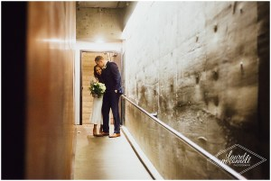Bride and groom embrace each other while having a quiet moment in a hallway at their wedding venue, Fremont Foundry, Seattle wedding, Perfectly Posh Events wedding planning, Photo by Laurel McConnell Photography