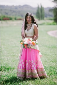 A blushing bride wears a traditional Hindu patterned pink wedding gown while holding an ivory, blush pink, and orange floral bouquet, Dairyland wedding, Snohomish county wedding, Hindu wedding, wedding planning by Perfectly Posh Events, Photo by Barrie Anne Photography