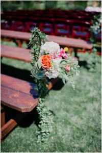 Rustic wood benches set up for a wedding ceremony are accessorized with white, pink, and orange and touches of greenery, Dairyland wedding, Snohomish county wedding, Hindu wedding, wedding planning by Perfectly Posh Events, Photo by Barrie Anne Photography